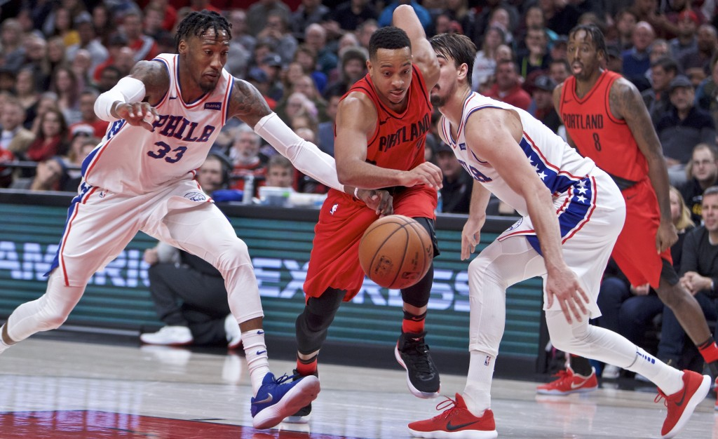 Portland Trail Blazers guard CJ McCollum, center, dribbles past Philadelphia 76ers forward Robert Covington, left, and forward Dario Saric, right, dur...