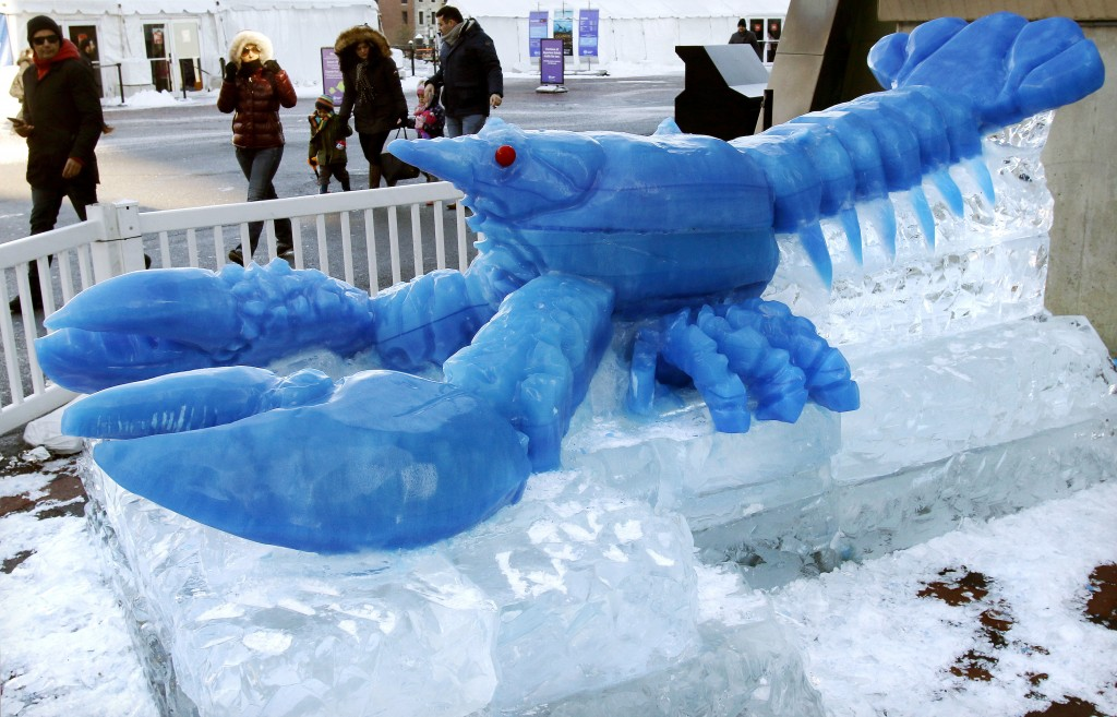 People walk past a blue lobster ice sculpture outside the New England Aquarium as the temperature hovers in the low teens, Thursday, Dec. 28, 2017, in...
