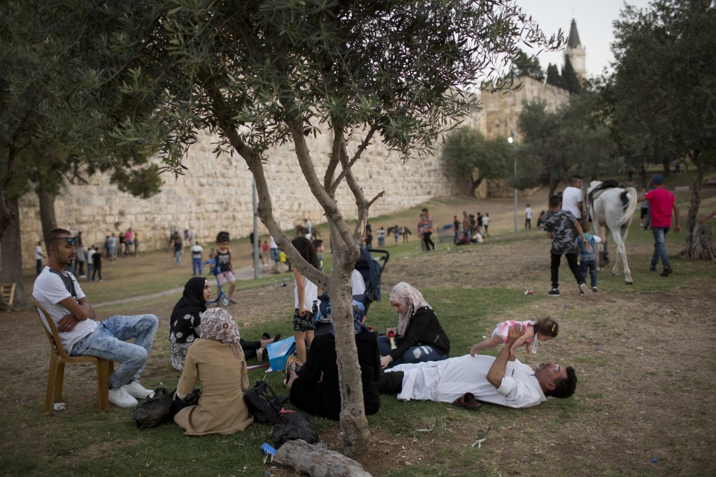 In this Tuesday, June 27, 2017 photo, Palestinians celebrates the Eid al-Fitr holiday outside Damascus Gate in Jerusalem. Jerusalem's iconic Old City ...