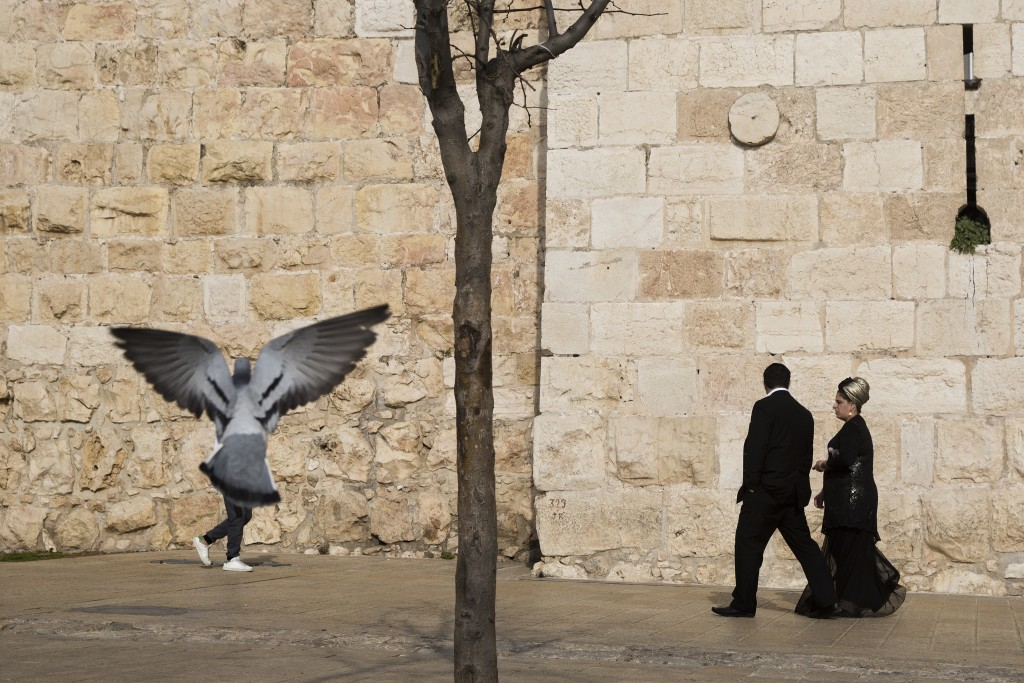 In this Saturday, Dec. 23, 2017 photo, people walk along the Jerusalem's Old City walls, next to Jaffa Gate. Jerusalem's iconic Old City walls have be...