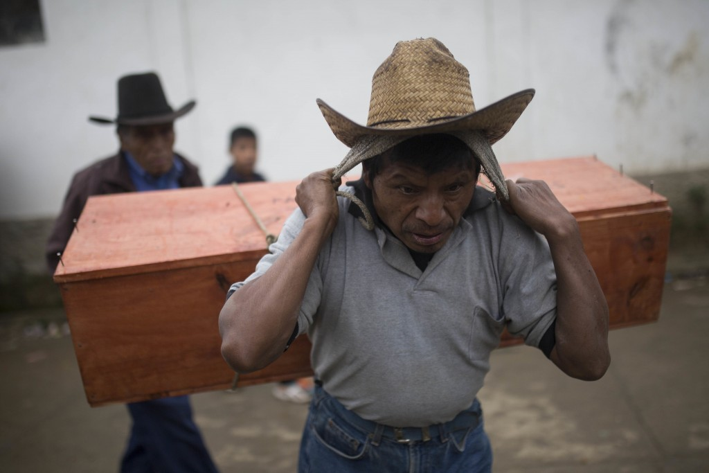 In this Nov. 30, 2017, an Ixil Mayan carries the remains of a civil war victim to a memorial for a mass burial in Santa Avelina, Guatemala. During the...