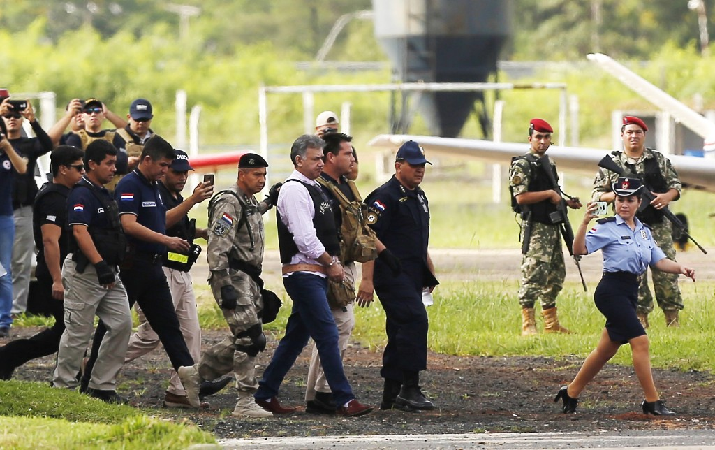 In this Dec. 28, 2017 photo, Brazilian drug lord Jarvis Chimenes Pavao, center, is escorted by Brazil's Federal Police officers to a plane at Silvio P...