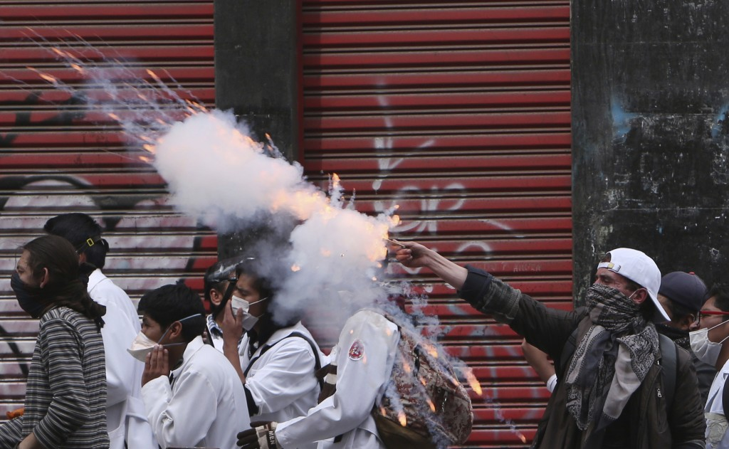In this Dec. 22, 2017 photo, a medical student fires fireworks towards the police during clashes supporting a strike by public doctors in La Paz, Boli...