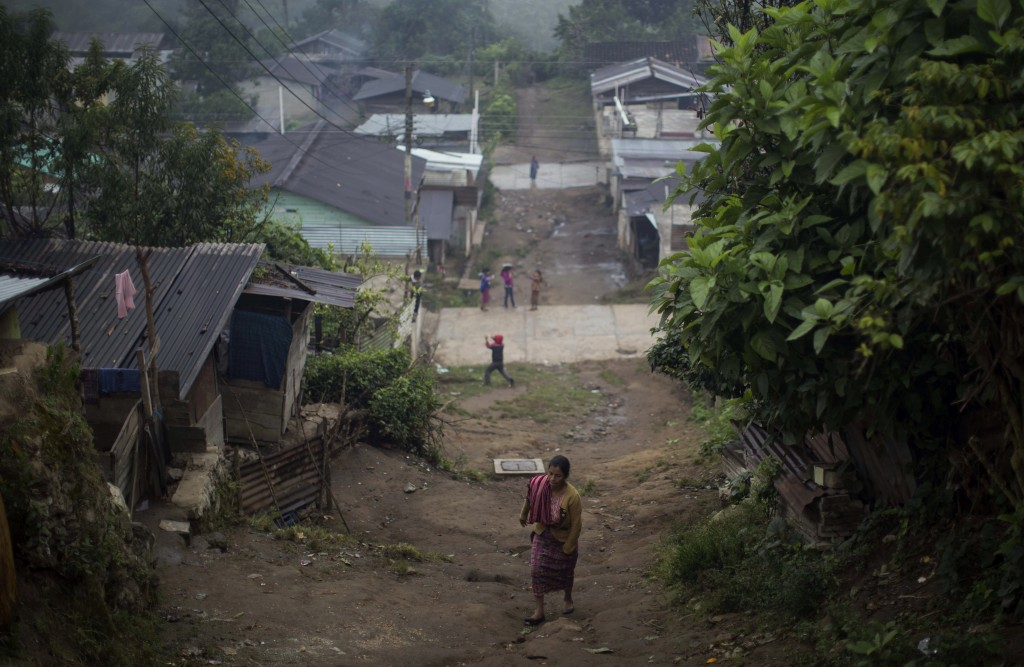 In this Nov. 30, 2017 photo, a woman walks up an unpaved road in the Ixil Mayan village of Santa Avelina, Guatemala. In 1980, the army formed one of i...