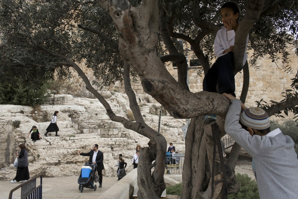 In this Tuesday, Dec. 19, 2017 photo, Israelis walks along the Jerusalem Old City walls during the Jewish holiday of Hanukkah. Jerusalem's iconic Old ...