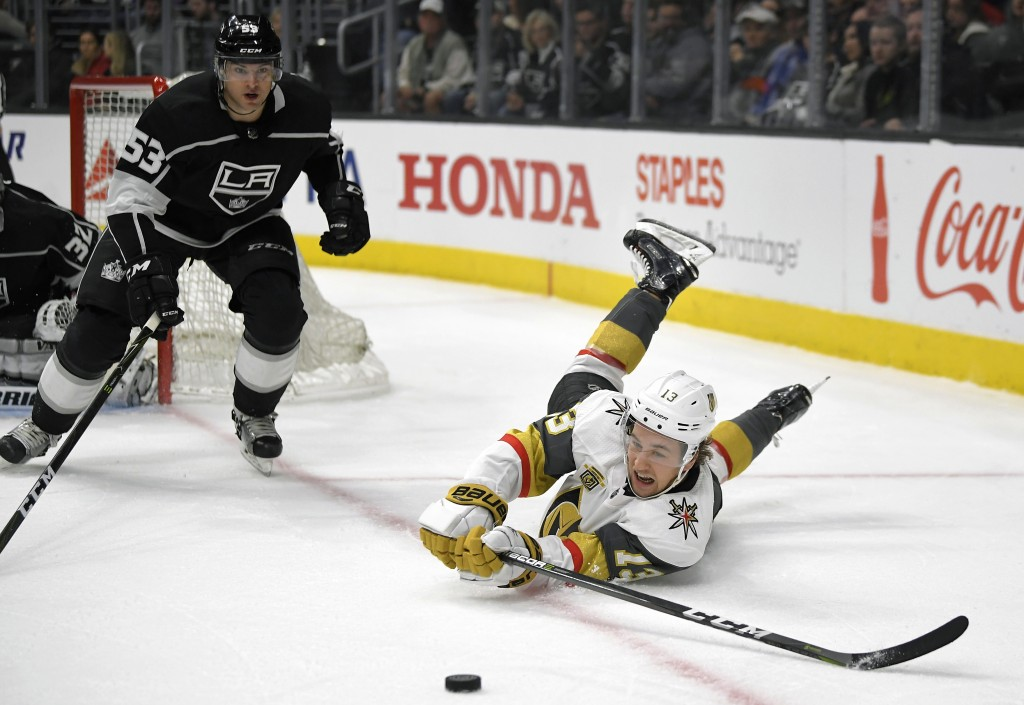 Vegas Golden Knights left wing Brendan Leipsic, right, falls as he passes the puck while under pressure from Los Angeles Kings defenseman Kevin Gravel...