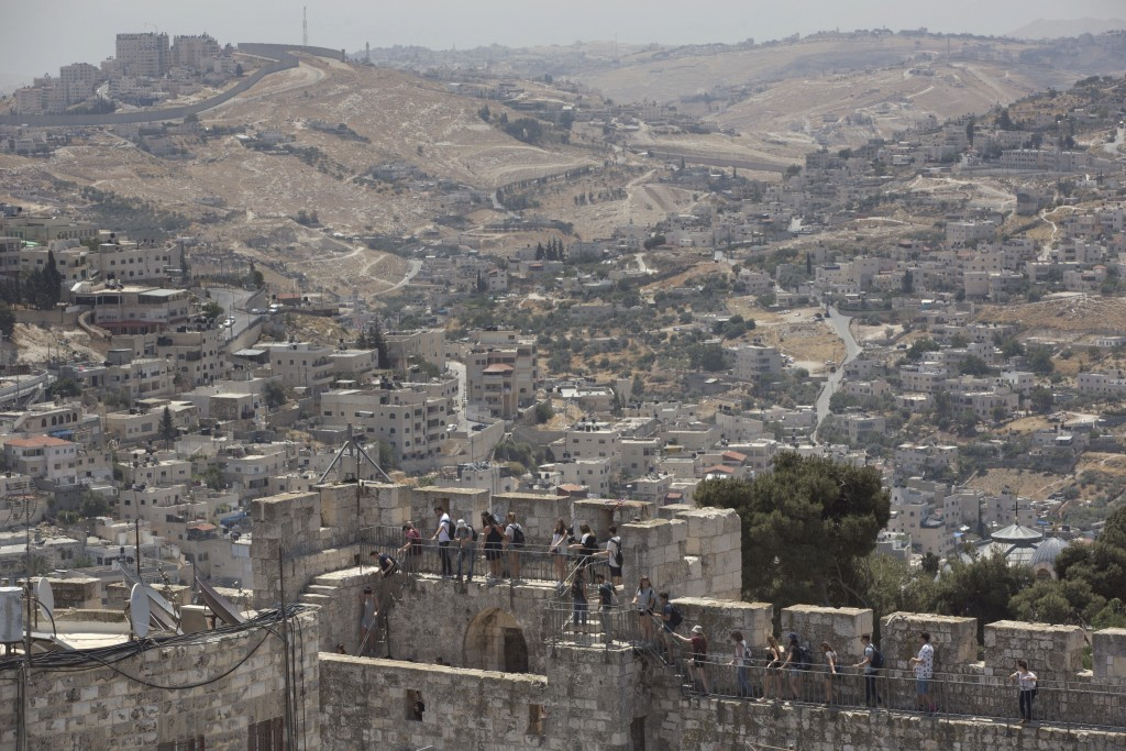 In this Wednesday, May 24, 2017 photo, Backdropped by the Silwan neighborhood of east Jerusalem, people tour the Jerusalem Ramparts Walk on Jerusalem'...
