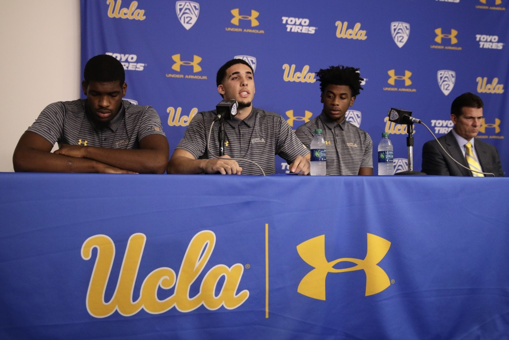 FILE - In this Nov. 15, 2017, file photo, Cody Riley, left, and Jalen Hill, third from left, flank UCLA basketball player LiAngelo Ball as he reads hi...