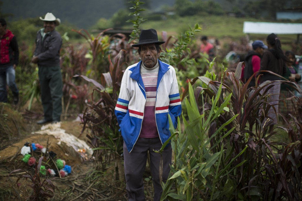 In this Nov. 30, 2017 photo, Tomas Cavinal Toma, 70, watches the burial of civil war victims at the cemetery in Santa Avelina, Guatemala. Exhumations ...