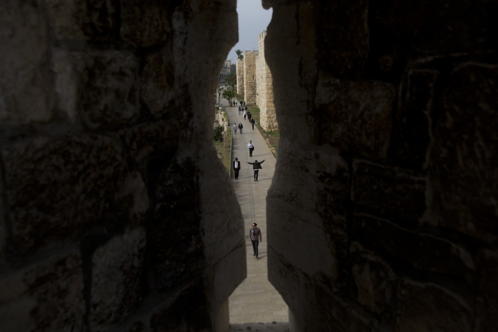 In this Saturday, Dec. 23, 2017 photo, people walk in and out Jerusalem's Old City seen trough the Old city walls in Jaffa Gate. Jerusalem's iconic Ol...