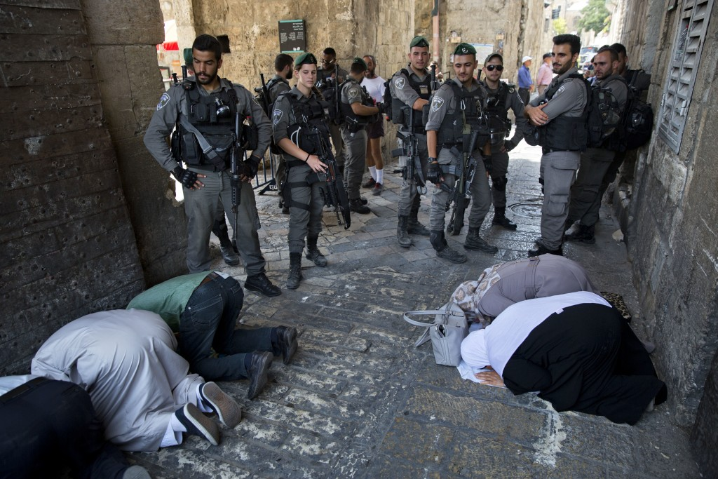 FILE - In this Tuesday, July 25, 2017 file photo, Palestinians pray as Israeli border police officers stand guard at the Lion's Gate in Jerusalem's Ol...