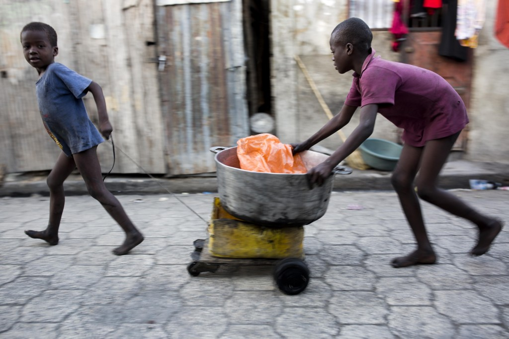 In this Dec. 27, 2017 photo, children transport a cooking bowl for their mother in the Cite Soleil slum of Port-au-Prince, Haiti. Cite Soleil is an ex...