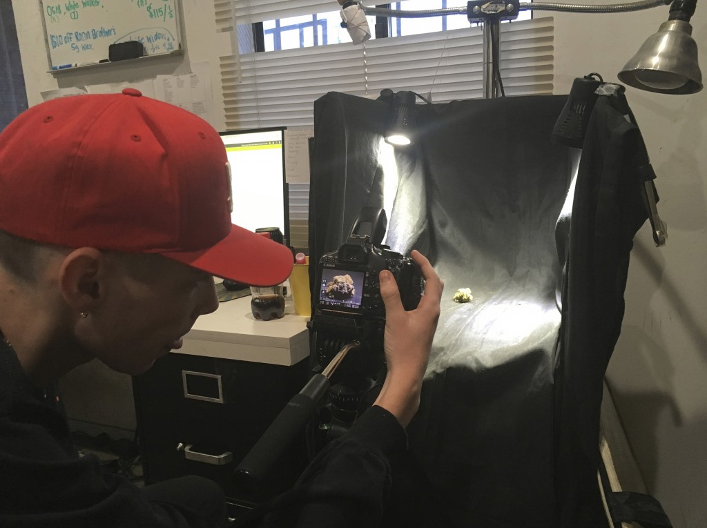"In this Wednesday, Dec. 27, 2017, photo employee Nate Johns photographs a ""Lamb's Bread"" marijuana bud for promotional use on the company's website at..."