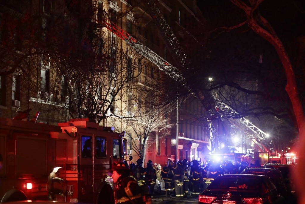 Firefighters respond to a building fire Thursday, Dec. 28, 2017, in the Bronx borough of New York. The Fire Department of New York says a blaze raging