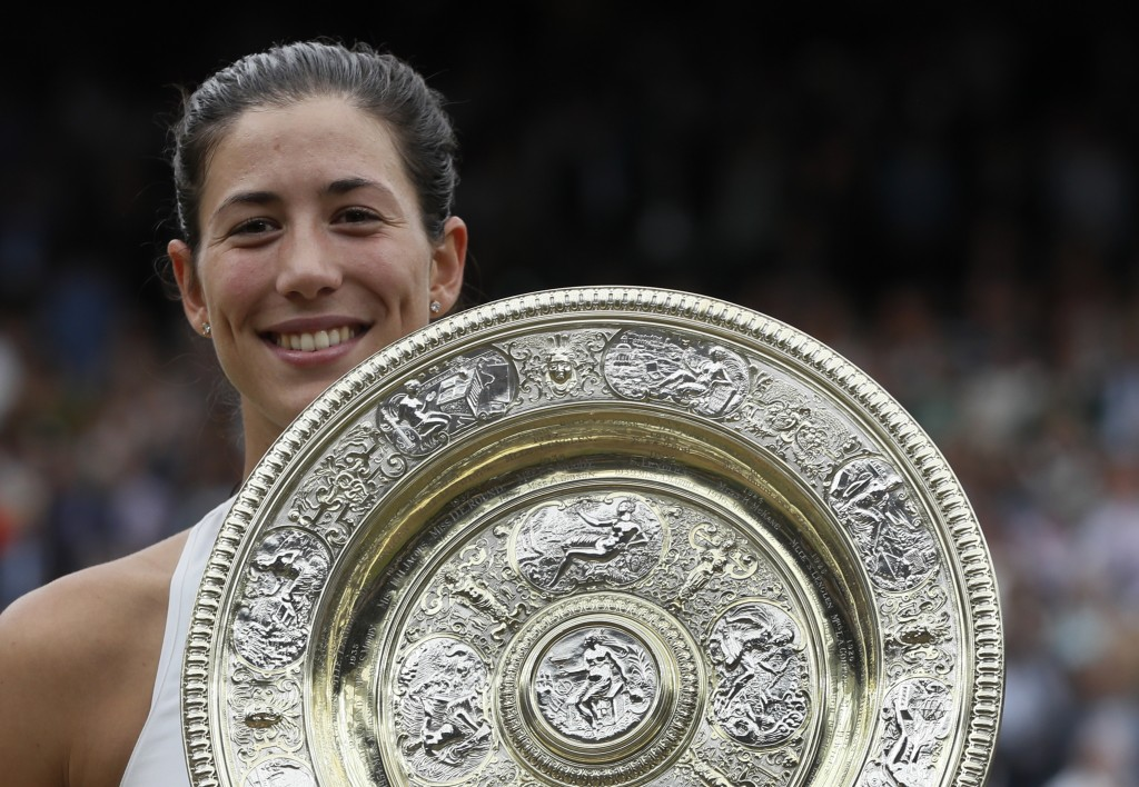 File- This July15, 2017, file photo shows Spain's Garbine Muguruza holding the trophy after defeating Venus Williams of the United States in the Women...