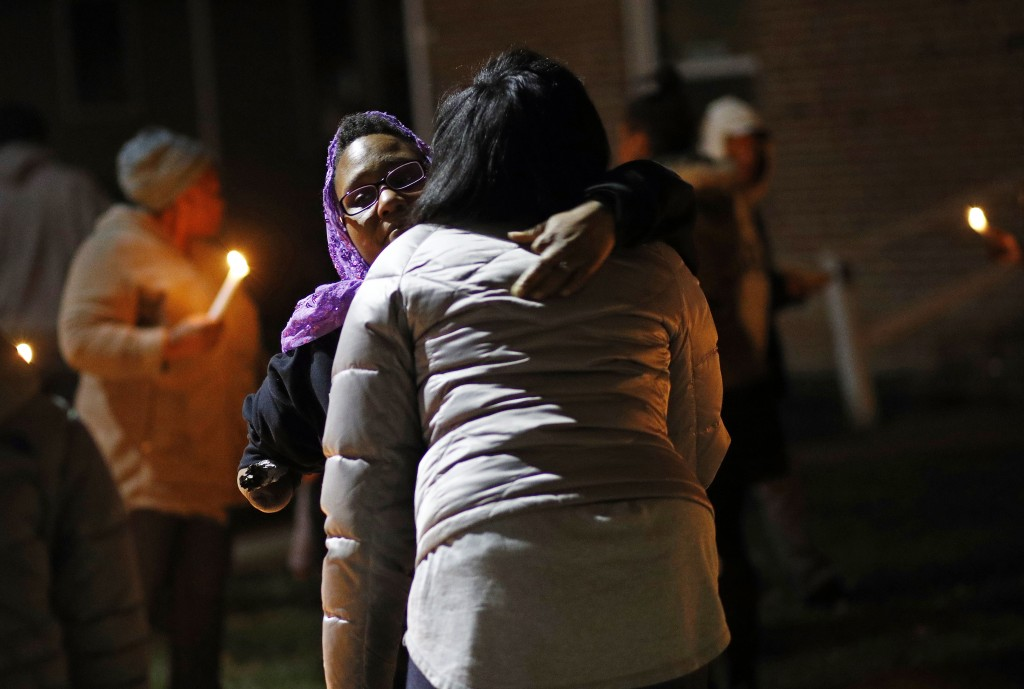 In this Dec. 22, 2017 photo, Erricka Bridgeford hugs a homicide victim's relative during a vigil near the site of the murder in Baltimore. Bridgeford ...