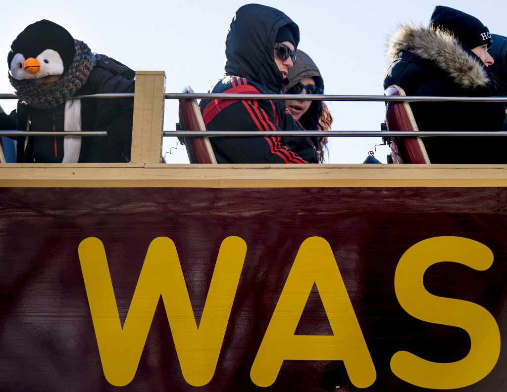People brave temperatures in the teens as they ride on an open air second level of a tourism bus as it makes its way down the National Mall, Thursday,...