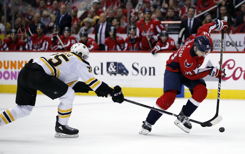 Boston Bruins defenseman Brandon Carlo (25) and Washington Capitals right wing Alex Chiasson (39) vie for the puck during the second period of an NHL ...