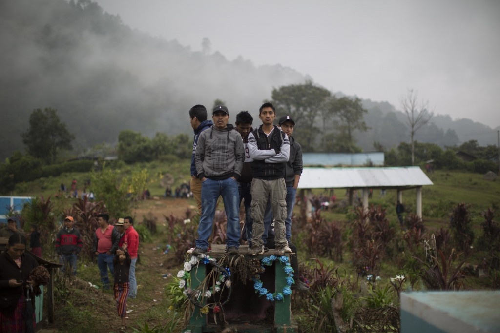 In this Nov. 30, 2017 photo, men stand on a cemetery tomb to get a better view of the burial of 172 Ixil Mayans who died during the civil war, in Sant...