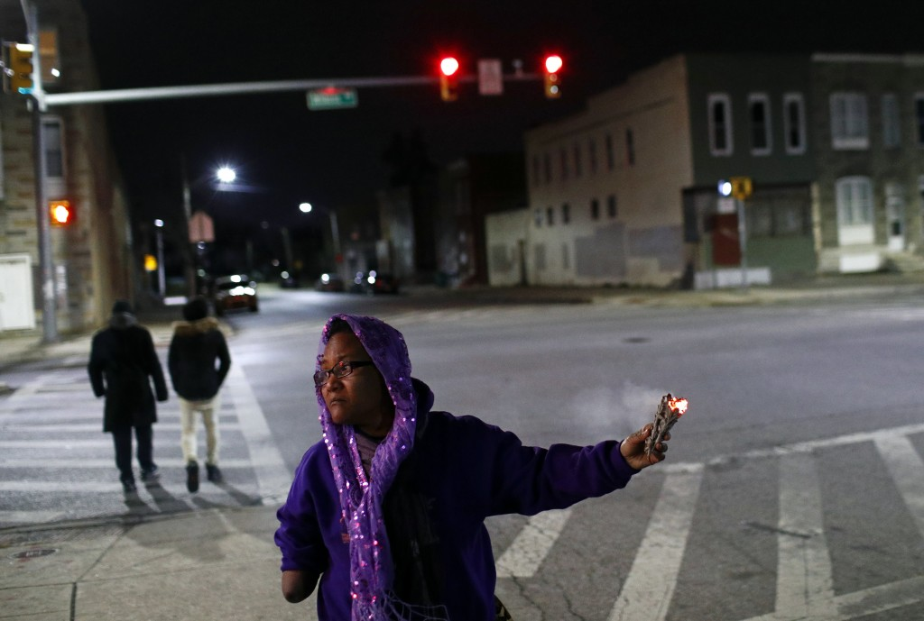 In this Dec. 14, 2017 photo, Erricka Bridgeford spreads sage as she performs a ceremony near the scene of a homicide in Baltimore. Bridgeford leads ne...