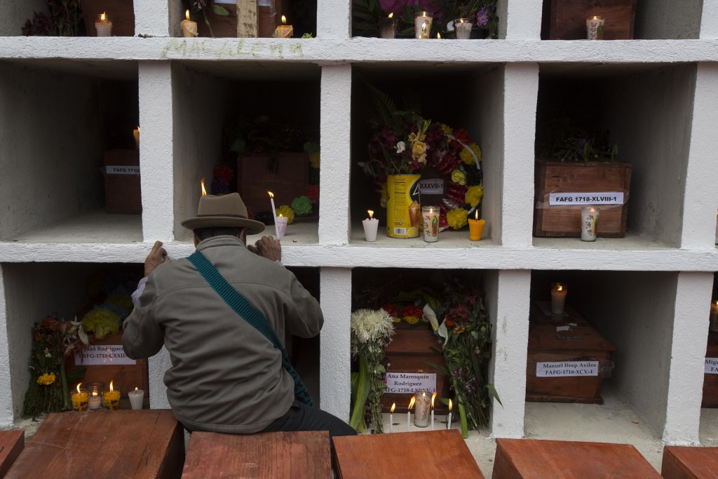 In this Nov. 30, 2017 photo, an Ixil Maya man prays next to the niches where 172 civil war victims were placed, at the cemetery in Santa Avelina, Guat...