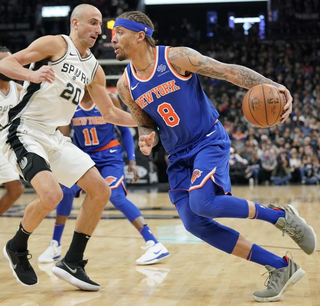 New York Knicks' Michael Beasley (8) drives against San Antonio Spurs' Manu Ginobili during the first half of an NBA basketball game, Thursday, Dec. 2...