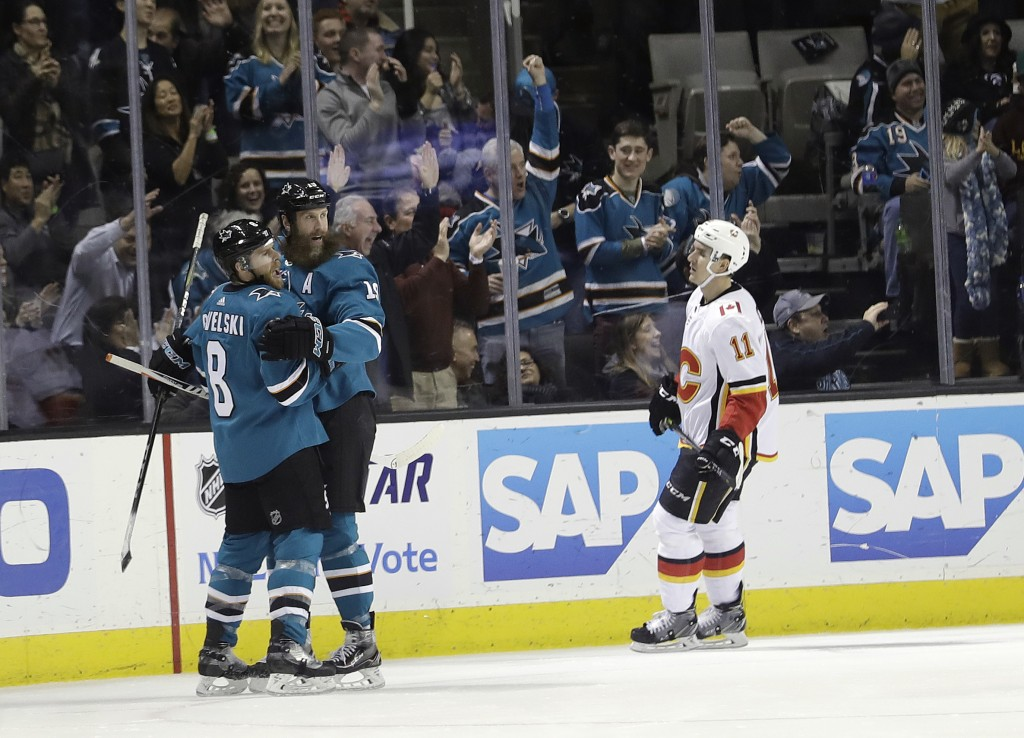 San Jose Sharks' Joe Pavelski, left, celebrates his goal with teammate Joe Thornton, center, while Calgary Flames' Mikael Backlund (11) skates past du...
