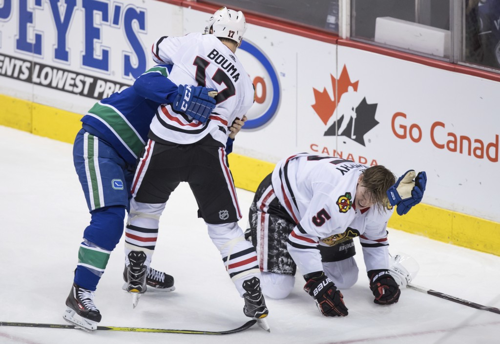 Chicago Blackhawks' Lance Bouma (17) and Vancouver Canucks' Alex Biega, left, fight after Chicago's Connor Murphy, right, was checked into the boards ...
