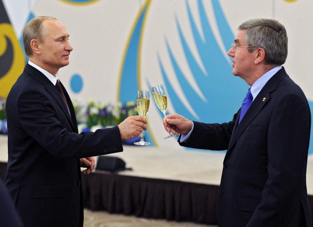 FILE - In this Feb. 24, 2014, file photo, Russian President Vladimir Putin, left, toasts a glass of champagne with the International Olympic Committee...