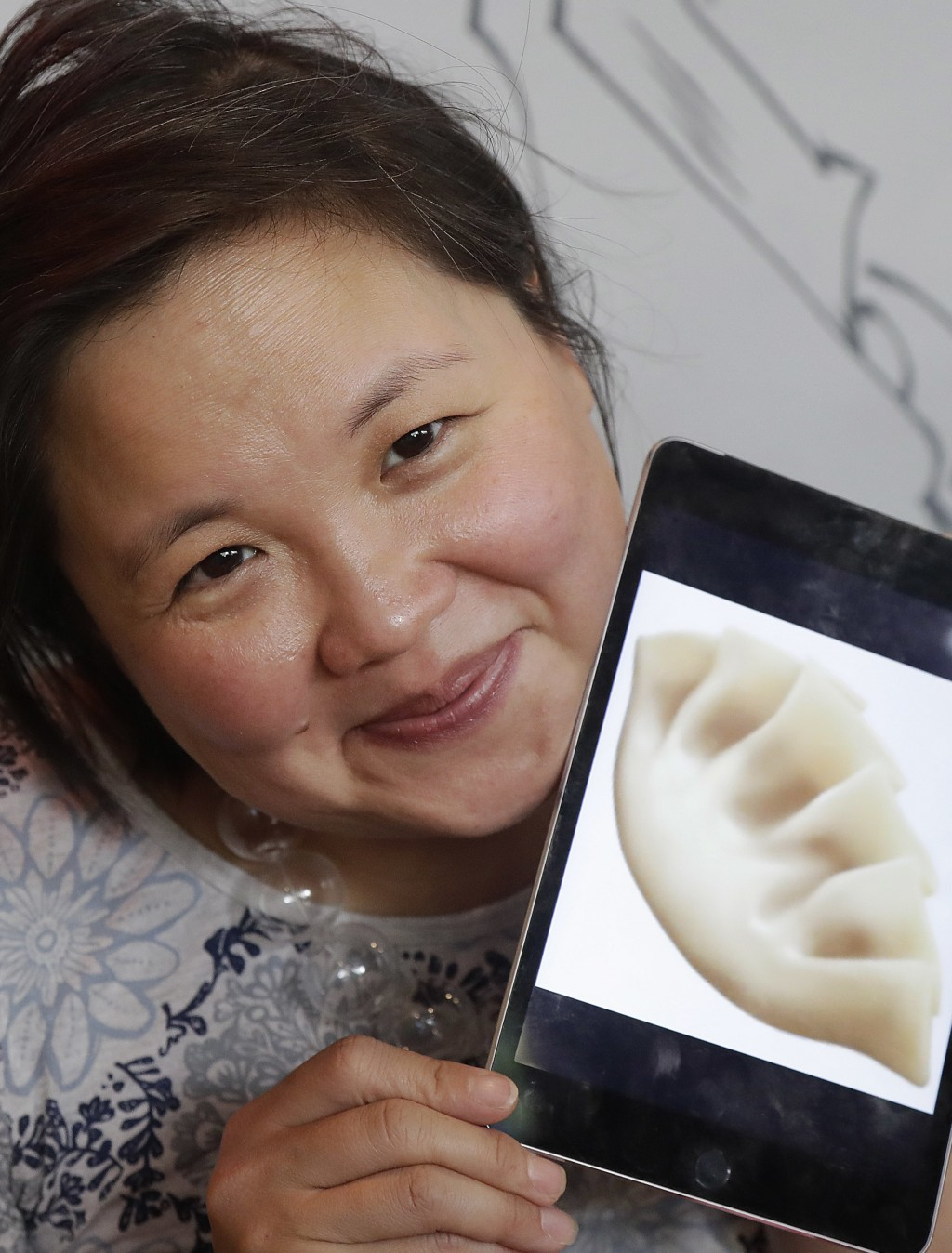 In this Wednesday, Dec. 27, 2017, photo, author Jennifer 8. Lee holds an image of a dumpling emoji while posing for photos before eating lunch at Dump...