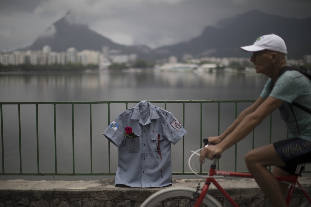 In this Dec. 27, 2017 photo, a man rides his bike past a police uniform shirt, stained in red representing spilt blood, as it hangs on a fence during ...