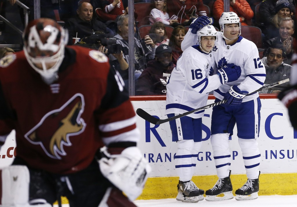 Toronto Maple Leafs center Patrick Marleau (12) celebrates his goal against Arizona Coyotes goalie Scott Wedgewood, left, with Maple Leafs center Mitc...