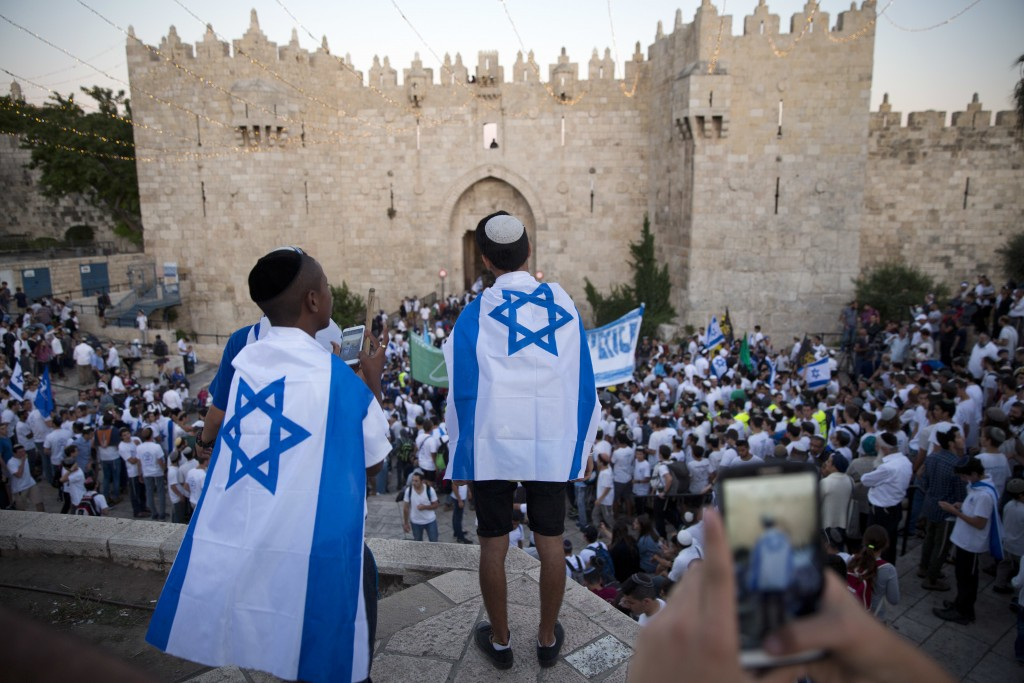 FILE - In this Wednesday, May 24, 2017 file photo, Israelis carry national flags outside the Old City's Damascus Gate in Jerusalem, during Jerusalem D...