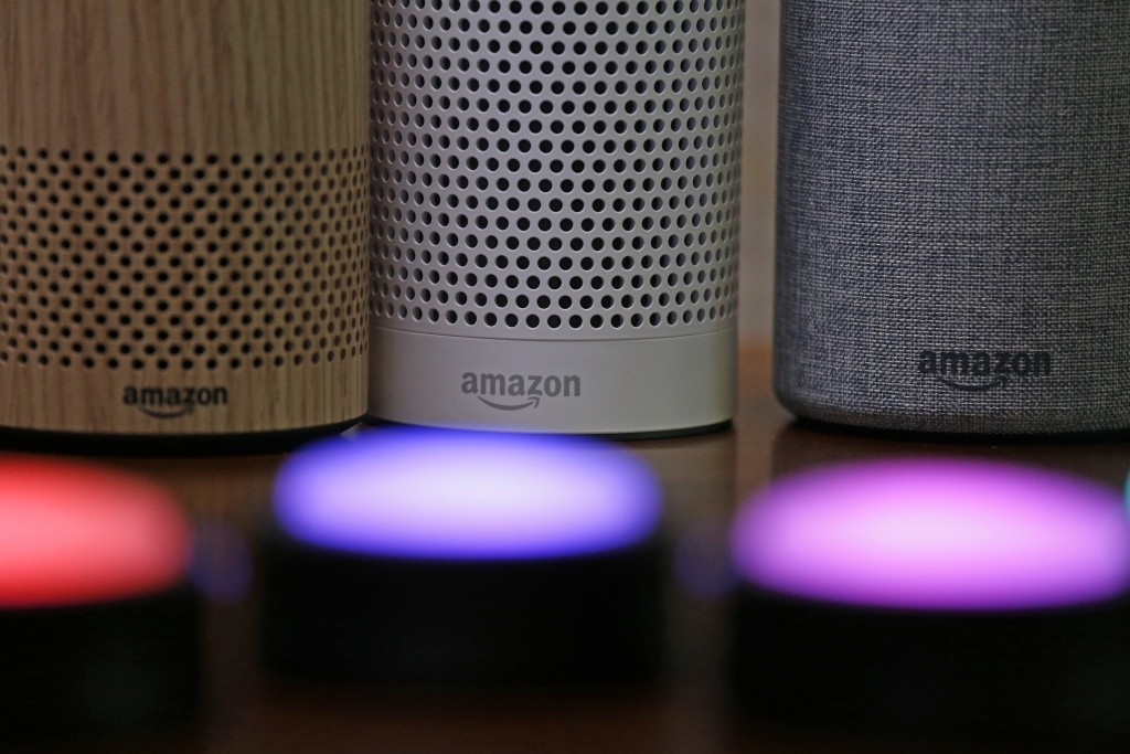 FILE - In this Wednesday, Sept. 27, 2017, file photo, Amazon Echo and Echo Plus devices, behind, sit near illuminated Echo Button devices during an ev...
