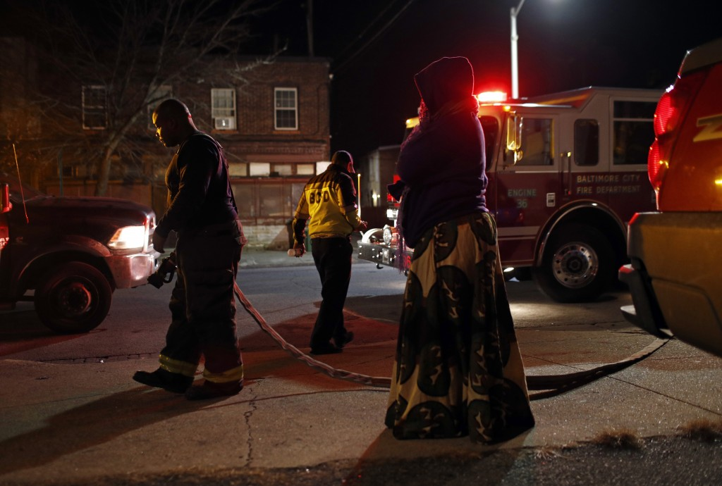 In this Dec. 14, 2017 photo, Erricka Bridgeford, right, watches as members of the Baltimore Fire Department prepare to wash away blood stains that wer...