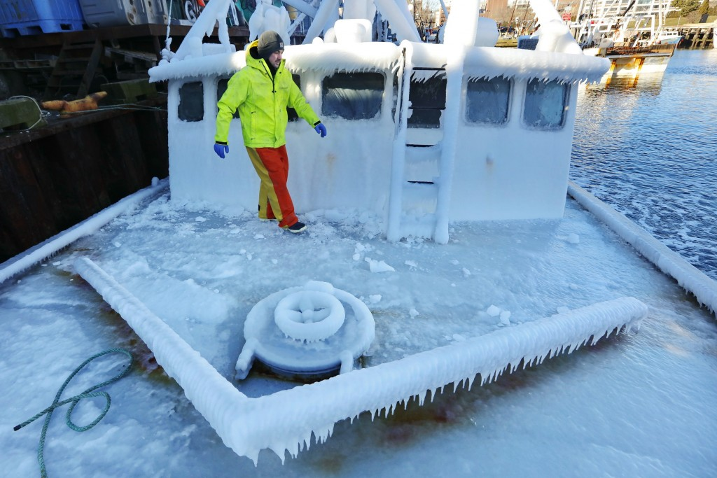 With temperatures in the single digits, Ray Levesque, mate of the crab/lobster boat Bradbill, makes his way across the deck covered in ice to tie off,...