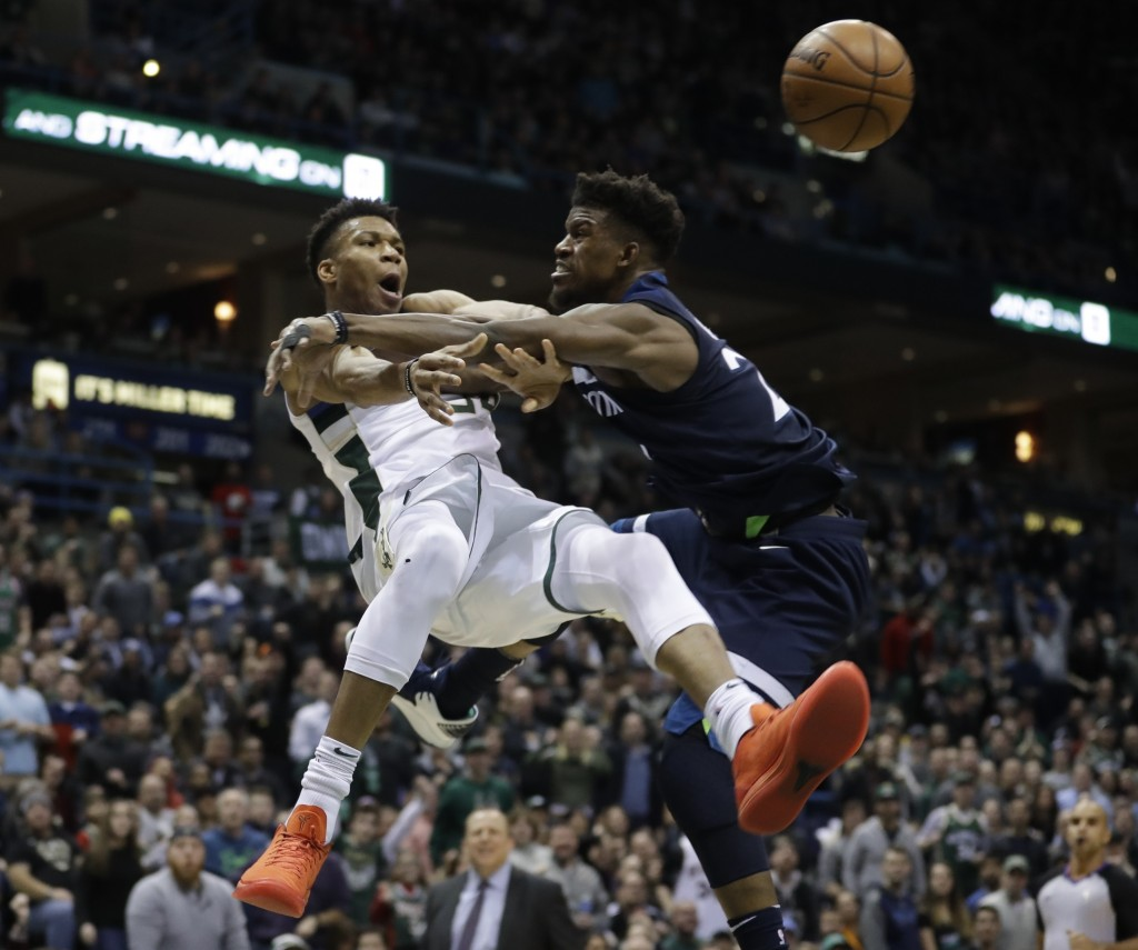 Milwaukee Bucks' Giannis Antetokounmpo is fouled by Minnesota Timberwolves' Jimmy Butler during the second half of an NBA basketball game Thursday, De...