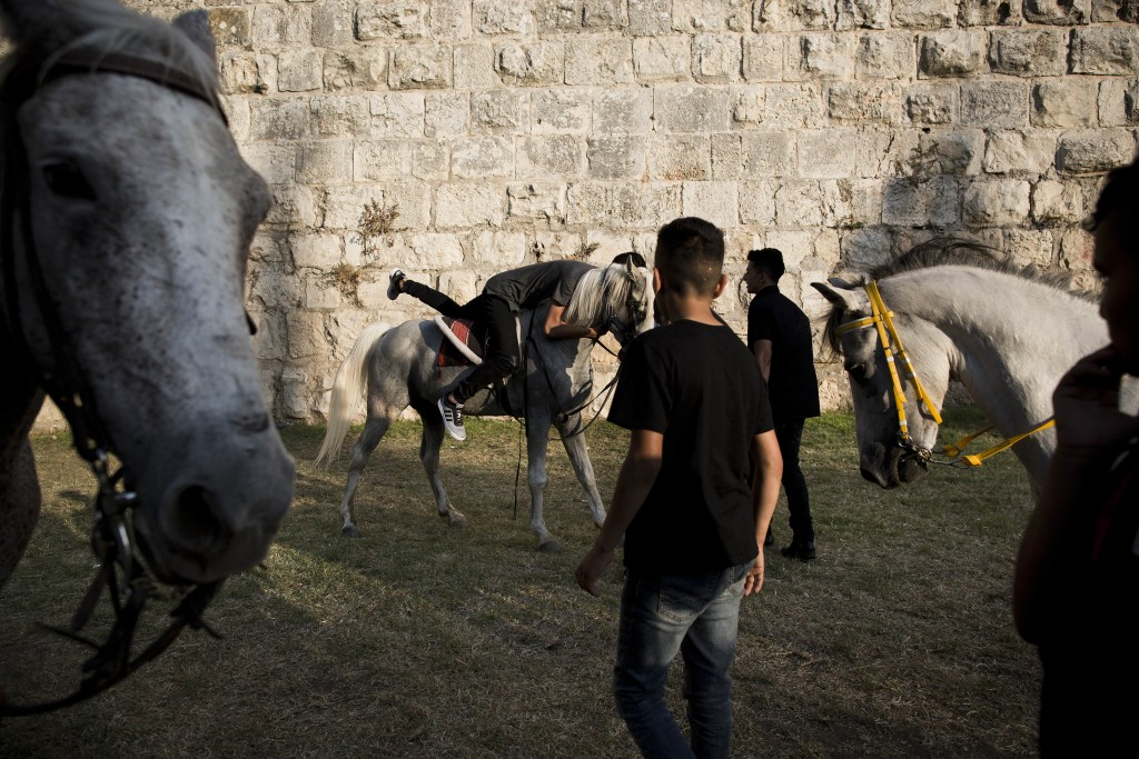 In this Tuesday, June 27, 2017 photo, Palestinians ride on horses during the Eid al-Fitr holiday outside Damascus Gate in Jerusalem. Jerusalem's iconi...