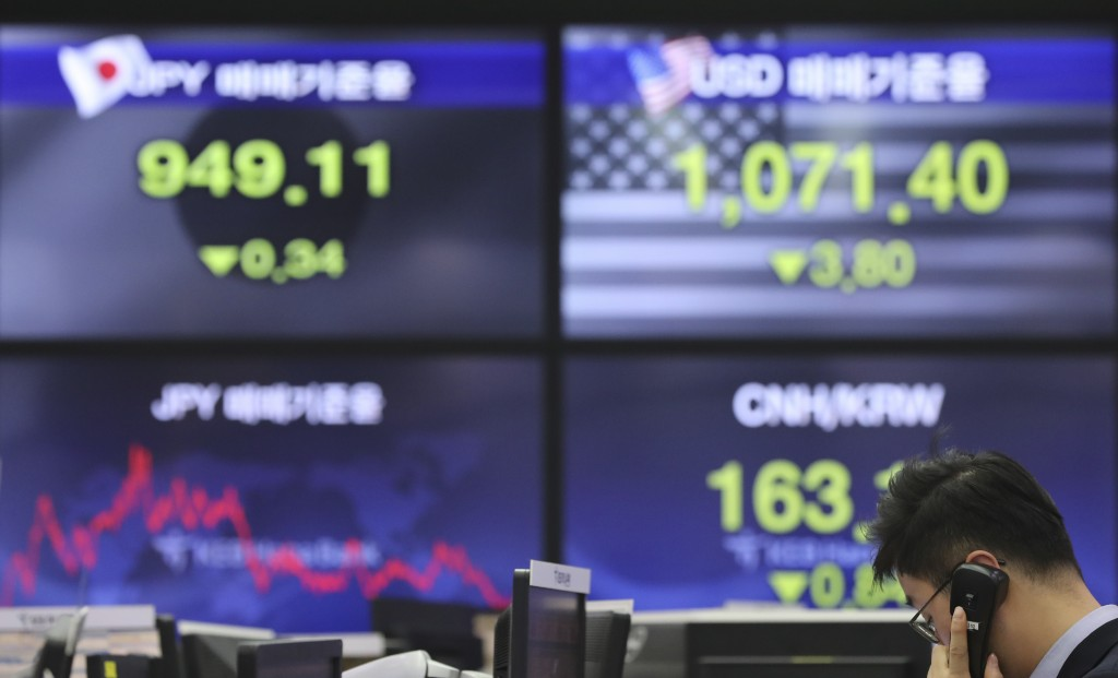 A currency trader talks on the phone near the screens showing the foreign exchange rates at the foreign exchange dealing room in Seoul, South Korea, F...