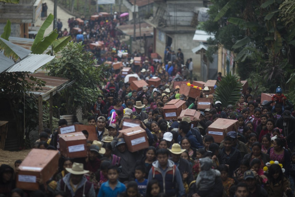 In this Nov. 30, 2017 photos, Ixil Mayans carry the remains of their loved ones killed during the civil war to the cemetery for burial in Santa Avelin...