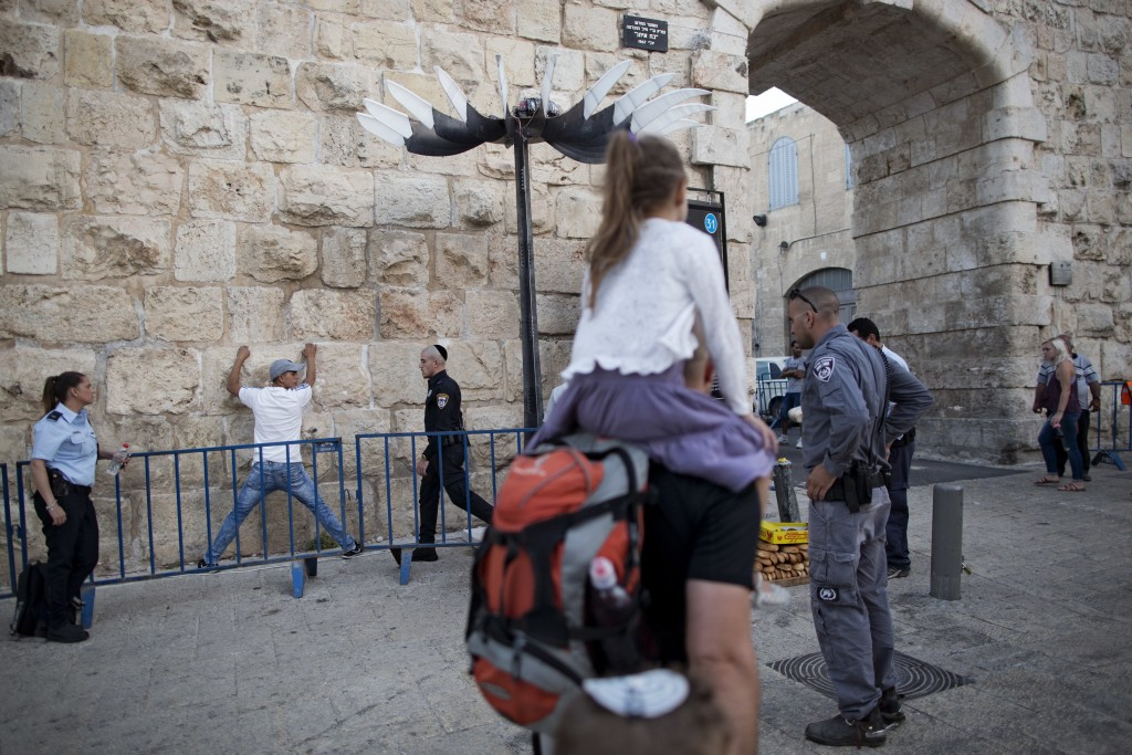 In this Thursday, July 6, 2017 photo, Israeli Police officers search a Palestinian man next to the New Gate in Jerusalem Old City. Jerusalem's iconic ...