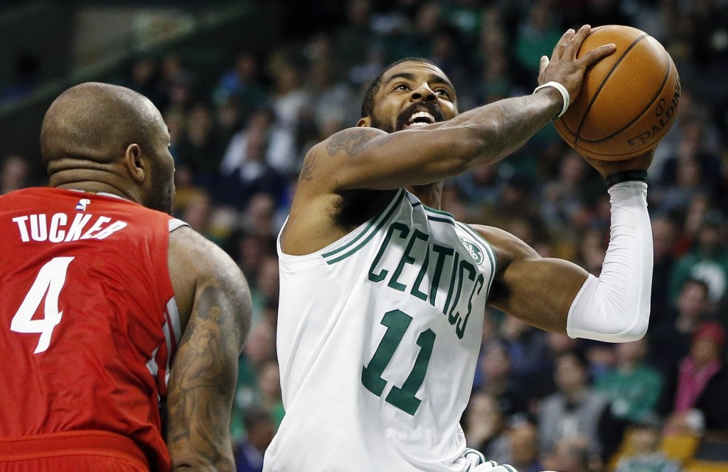 Boston Celtics' Kyrie Irving (11) shoots in front of Houston Rockets' PJ Tucker (4) during the second quarter of an NBA basketball game in Boston, Thu...