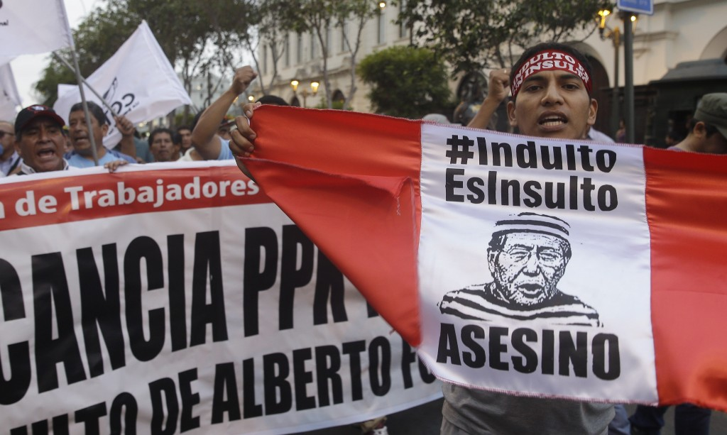 """Demonstrators shout slogans against the pardon of former President Alberto Fujimori while holding the flag of Peru that reads in Spanish: """"Pardon is I..."""