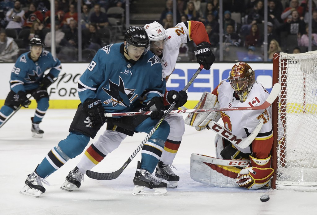Calgary Flames goalie David Rittich, right, stops a shot in front of teammate Travis Hamonic, center, and San Jose Sharks' Tomas Hertl during the seco...