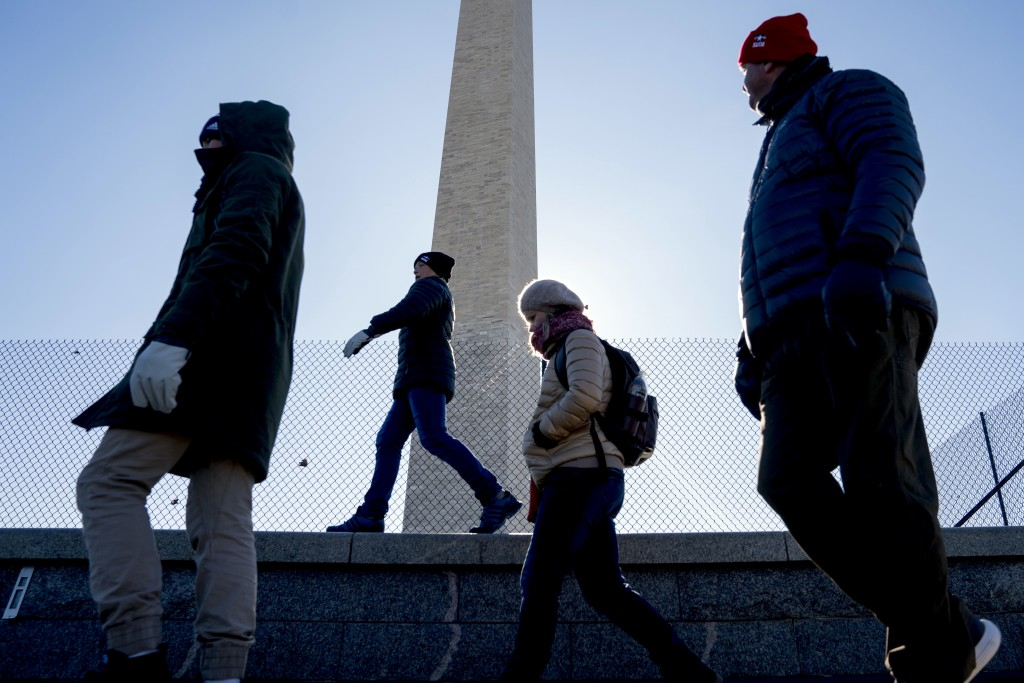 Visitors to the Washington Monument on the National Mall brave temperatures in the teens, Thursday, Dec. 28, 2017, in Washington. (AP Photo/Andrew Har...