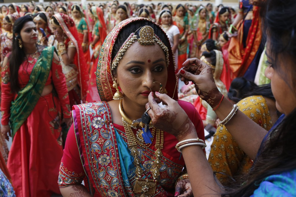 In this Dec. 24, 2017, file photo, a bride is helped before a mass wedding in Surat, India. Two hundred and fifty one young couples, including five Mu...