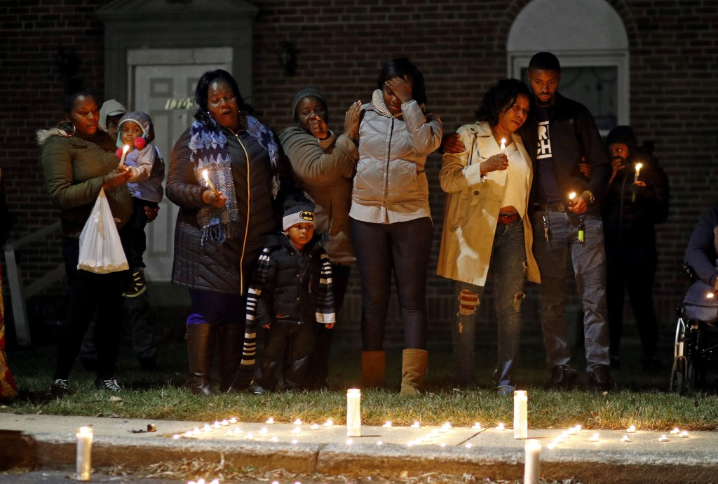 In this Dec. 22, 2017 photo, relatives of a homicide victim gather for a vigil near the scene of the murder in Baltimore. Friends and family of the vi...