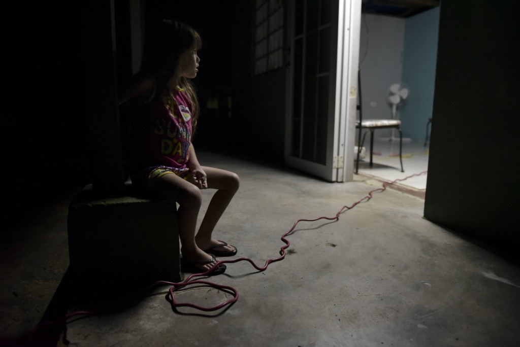 In this Dec. 21, 2017 photo, six year old Melanie Oliveras González remains seated on the balcony of her house, in Barrio Patrón, Morovis, Puerto Rico...