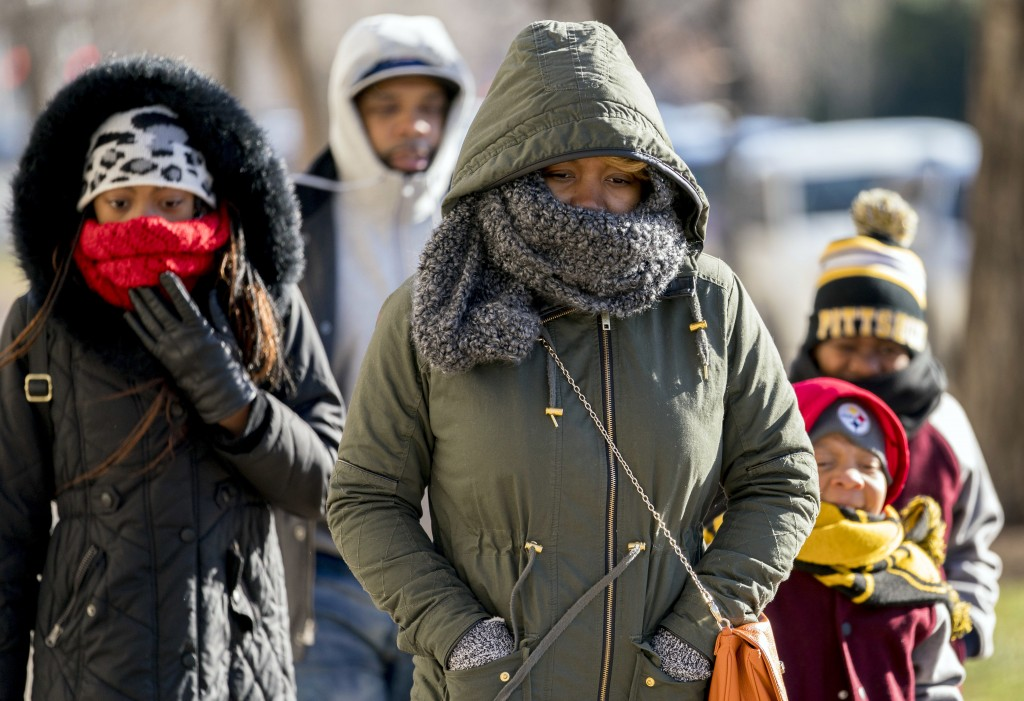 A family braves temperatures in the teens as they make their way to the National Museum of African American History and Culture on the National Mall, ...