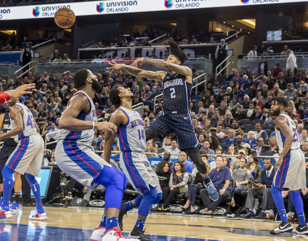 Orlando Magic guard Elfrid Payton (2) passes the ball over Detroit Pistons guard Ish Smith (14) and center Andre Drummond, front left, during the firs...